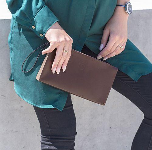 Hnedovlasá modelka s elegantnou koženou listovou kabelkou a drevenou listovou kabelkou