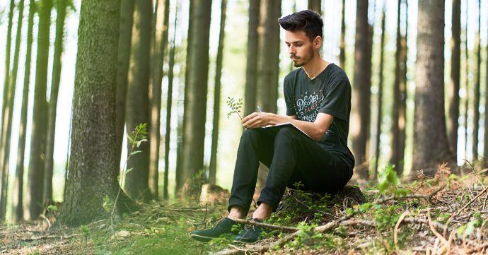 Muž sediaci v lese a píše do BeWooden zápisníku