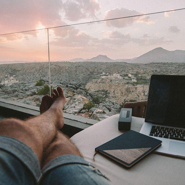 Muž sedí pri okne a vedľa seba má zápisník Ocean Notebook