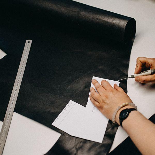 Žena vyrezáva kožené časti na výrobu peňaženky