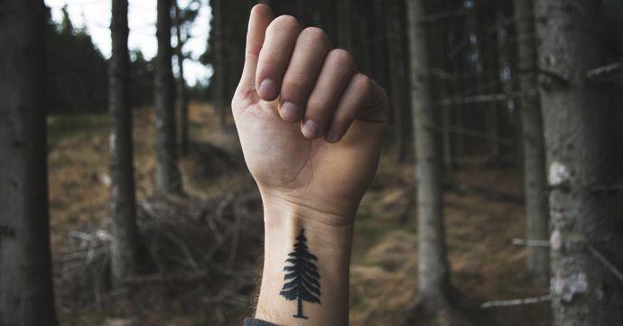 Muž v lese s vytetovaným stromom na ruke