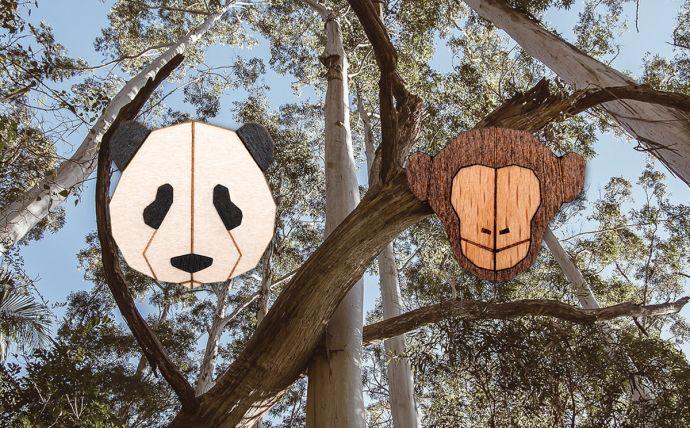Drevené brošne opica a panda na obrázku tropickej prírody
