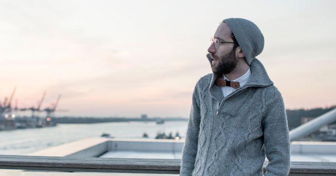 Muž stojaci vonku v šedom svetri a čiapke má na krku drevený motýlik
