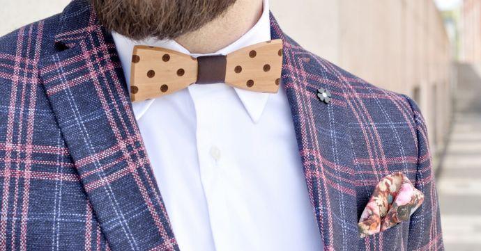 Muž v kockovanom saku s bodkovaným dreveným motýlikom Dolo